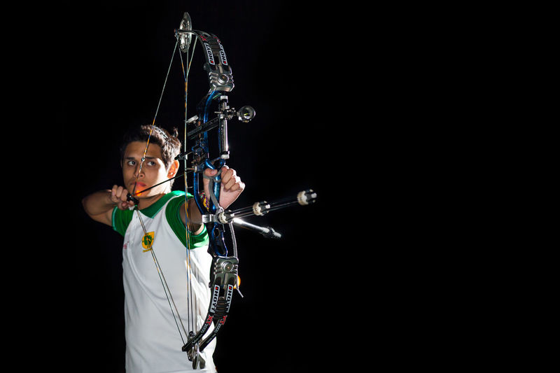 A sport portrait of a young archer from the Yucatan Archery delegation Sportsman Archer Archery Archery Bows Archery Competition Black Background Front View One Person Performance Portrait Skill  Sport Sports Photography Standing Studio Shot Young Adult