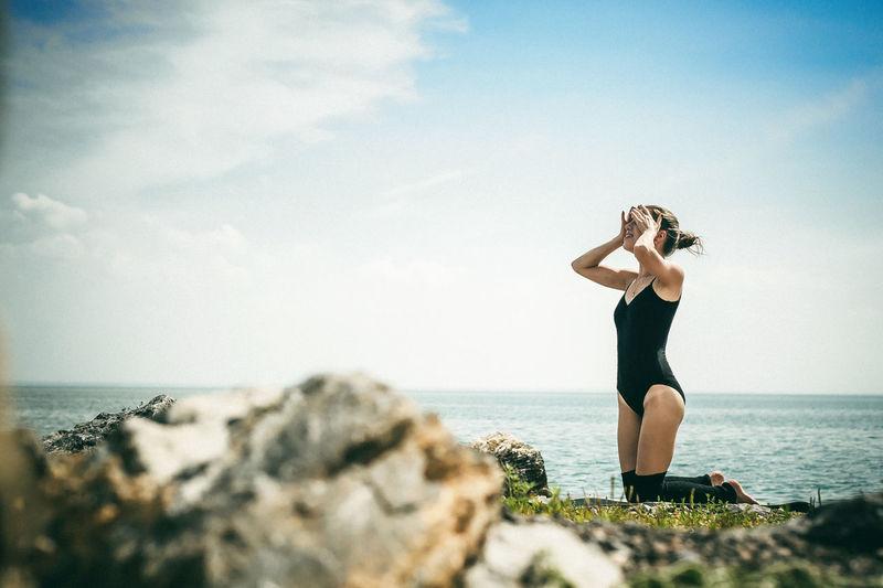 Woman kneeling at beach against sky