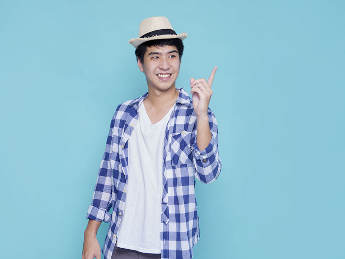 Portrait of smiling young man against blue background