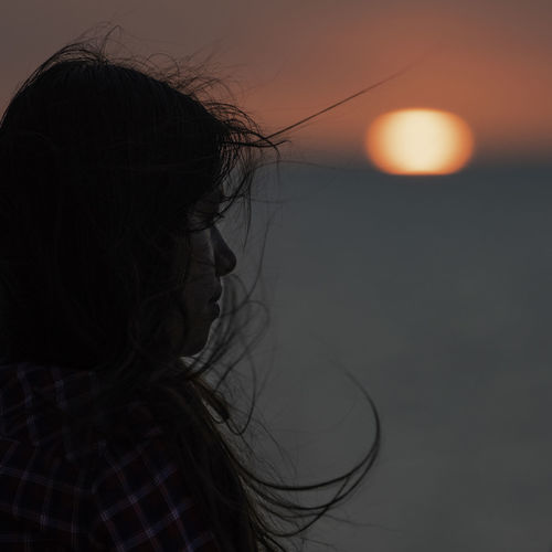 Close-up of woman against sky during sunset