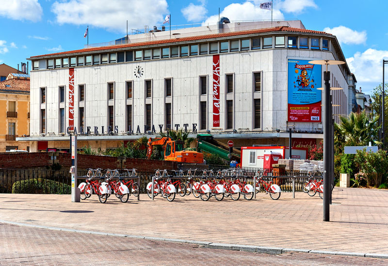Perpignan, France - April 8; 2016: Exterior of shopping mall in Perpignan downtown. Pyrenees-Orientales Advertisement Architecture Bike City Day Downtown Editorial  Facade Building France Languedoc-Roussillon Mall Midi-Pyrenees Perpignan Pyrénées-Orientales Rental Bicycle Roussillon Shopping Centre Sidewalk Signboard Springtime Street Sunlight Urban Landscape Walkway Western Europe