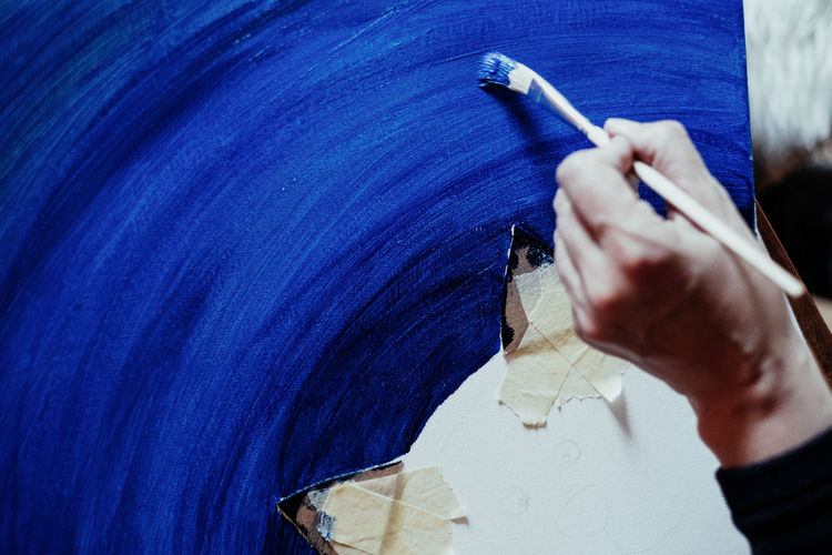 In Blue Blue Indoors  Close-up Creativity Art And Craft Painting Art One Person Real People Hand Human Hand Holding Human Body Part Lifestyles Pen Unrecognizable Person Paper Skill  Leisure Activity Brush Paintbrush Springtime Decadence