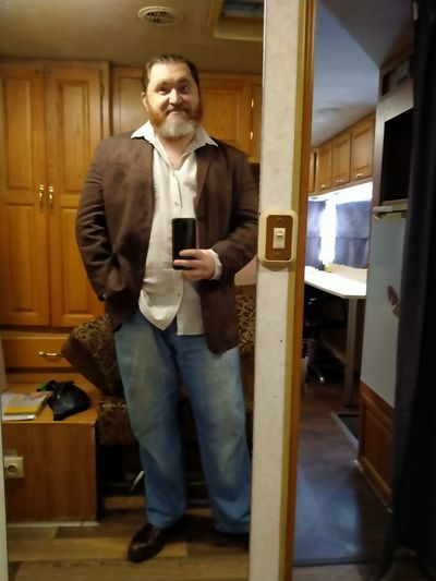 Full length portrait of young man standing at home