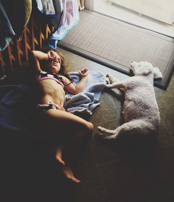 High angle view of girl in bikini lying down by dog on floor