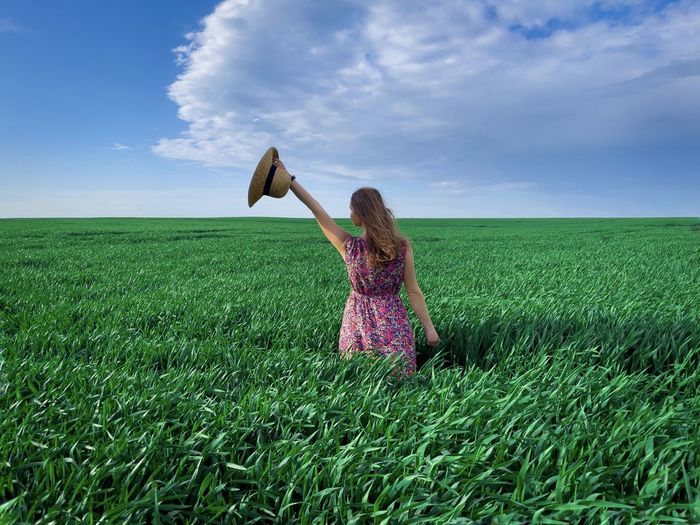 Rear view of woman wearing dress and hat in a field of green wheat