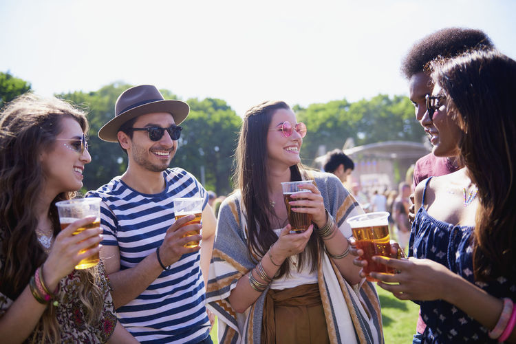 Friends holding drinks in glasses while standing against sky