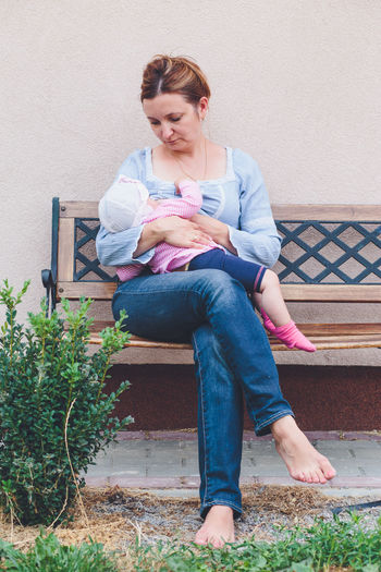 Mother breast feeding daughter while sitting on bench in yard
