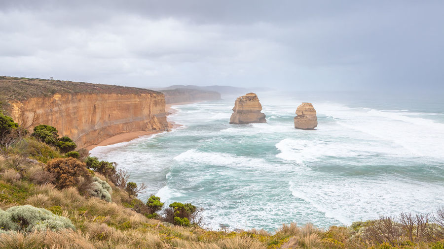 Scenic view at the Twelve Apostles Autumn colors Stormy Weather Beach Beauty In Nature Cloud - Sky Day Eroded Horizon Over Water Land Limestone Rocks Motion Nature Outdoors Rock Rock - Object Rock Formation Scenics - Nature Sea Sky Solid Stack Rock Storm Clouds Surfing Water Wave