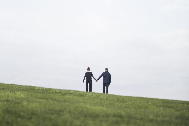 Couple standing on field against sky