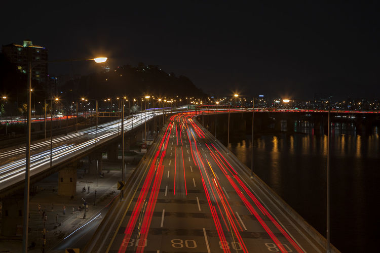 High angle view of light trails on road by river in city at night