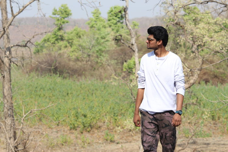 Young man looking away while walking on field against trees