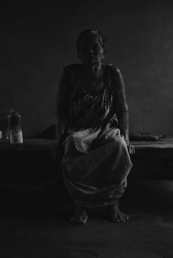 Woman sitting on table against dark background