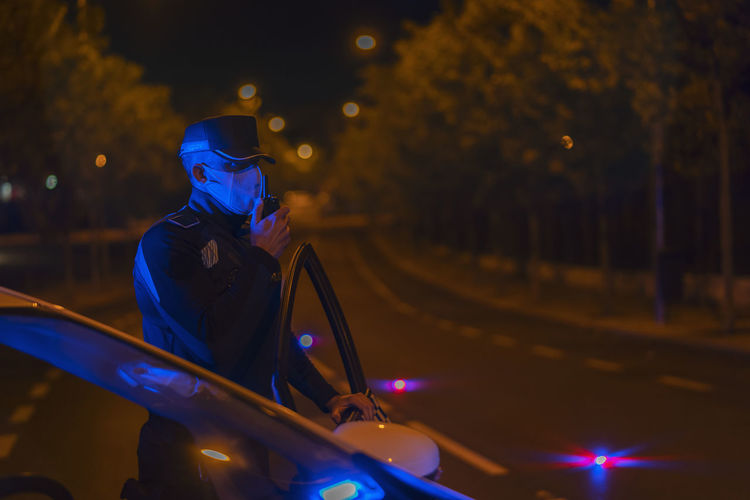 Man riding motorcycle on illuminated street at night