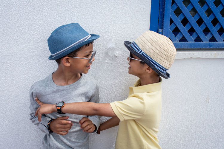 Two boys in hats having fun in the sun. Architecture Boys Cap Casual Clothing Child Clothing Day Hat Leisure Activity Males  Men People Profile View Side View Standing Togetherness Two People Waist Up Wall - Building Feature Young Adult