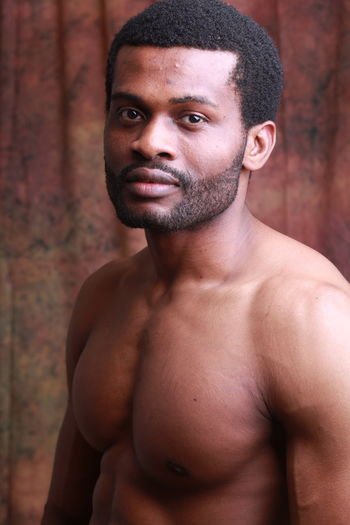 Shirtless Man Standing Against Wall