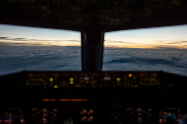 Airplane window against sky during sunset