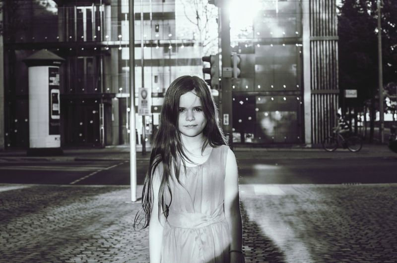 Young woman standing on street at night