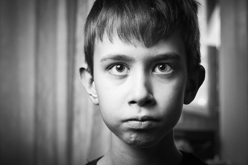 Close-Up Portrait Of Serious Boy At Home