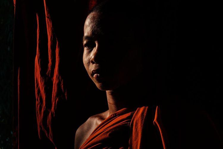 A portrait of a young novice monk in a monastery in Mohnyin, Myanmar. Jan 2018. Myanmar Burma Mohnyin Monk  Novice Monk Monastery Portrait Light Black Background Portrait Shadow Human Face