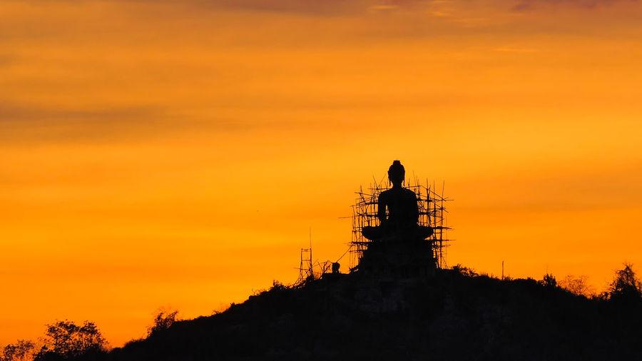 Building buddha on mountain at sunset