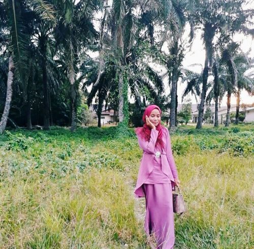 Malaysian Culture Traditional Clothing Pink Hotpink Scarf Grass Pink Color Leisure Activity Outdoors Tree Nature Fashion Stories Day Beautiful Woman Real People Lifestyles