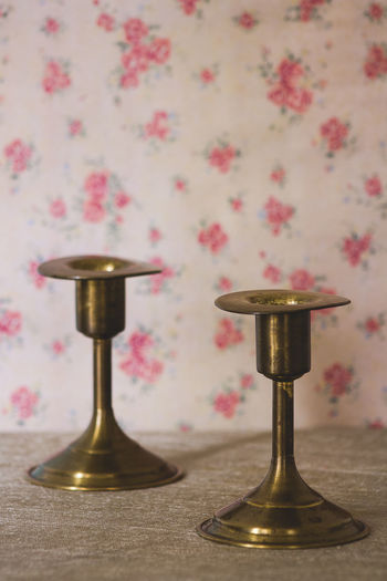Indoors  No People Table Metal Still Life Pattern Wall - Building Feature Wallpaper Floral Pattern Close-up Pink Color Gold Colored Home Interior Brass Flower Lighting Equipment Two Objects Candle Plant Vintage Candelabro Orange Color Tapiz