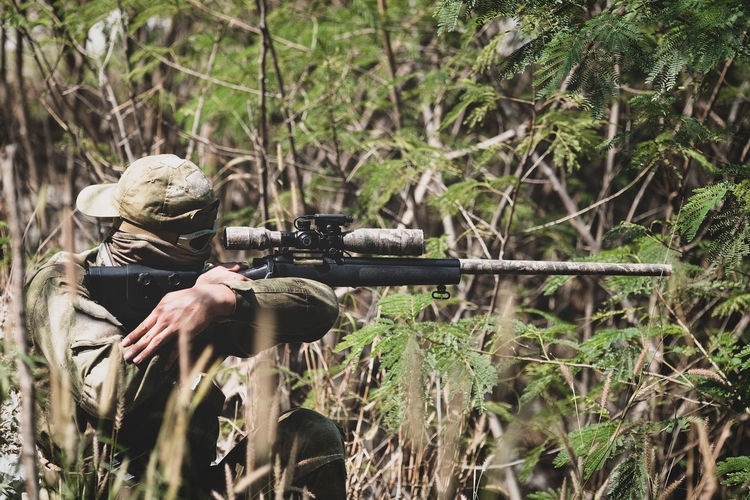 Fully Equipped Soldiers Wearing Camouflage Uniform Attacking Enemy, Airsoft military game player in camouflage uniform Gun Aiming Plant Weapon Rifle Land One Person Nature Real People Shooting A Weapon Forest Tree Military Security Day Safety Holding Government Camouflage Clothing Outdoors Hunter Uniform