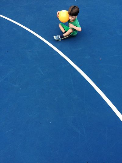 High angle view of boy with ball sitting at tennis court