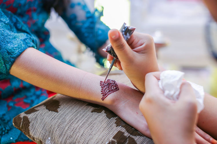 Cropped image of beautician making henna tattoo on woman hand