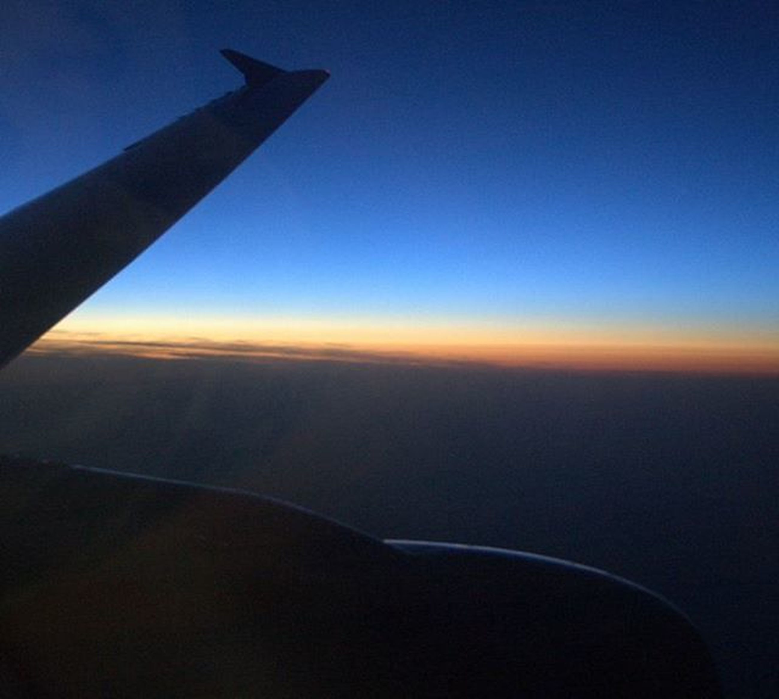 airplane, transportation, air vehicle, aircraft wing, flying, mode of transport, part of, aerial view, cropped, sky, mid-air, travel, journey, scenics, landscape, sunset, beauty in nature, on the move, public transportation, blue