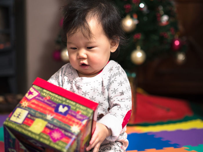 Cute baby girl with christmas gift at home