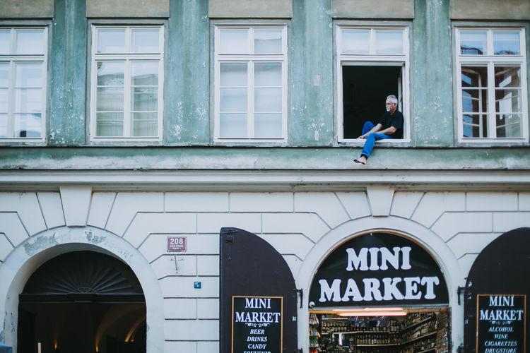 A man sitting by the window. Cityscape Czech Republic Prague Building Lifestyles Mini Market Shop Store Window