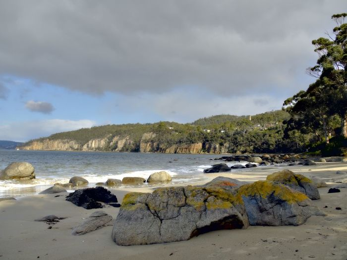 Bright colored rocks on the beach and the Taroona Shot Tower in the distance Beach Beauty In Nature Bright Colors Rocks Taroona Tasmania Cliff Sand EyeEm Nature Lover Clouds And Sky Waves, Ocean, Nature Waves Rock - Object Get Outside Hidden Gems  No People Colours Nature's Colours  Lichen On A Rock Lichen