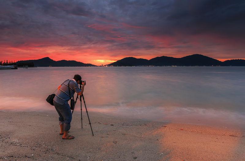 Rear view of photographer on beach against cloudy sky