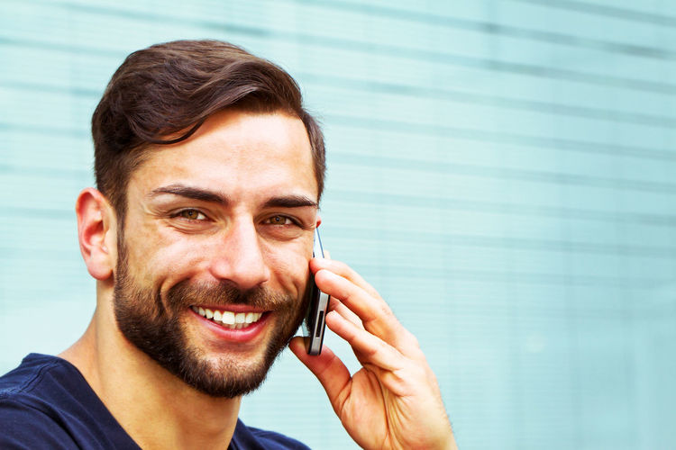 Young, modern man with smart phone Business City Handy Happy Man Modern Architecture Young Beard Call Cheerful Communication Finance Handsome Happiness Headshot Looking At Camera Men Outdoors Phone Portrait Smart Phone Smiling Technology Using Phone Young Adult