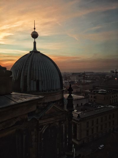 Berlin cathedral by residential district against sky during sunset