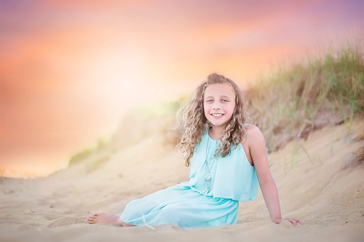 Portrait of smiling girl on sand at sunset