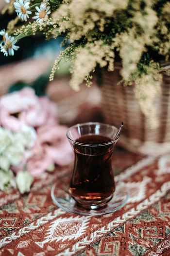 Glass cup of turkish black tea on table with pattern and flowers