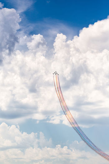 Low angle view of fighter planes performing airshow in cloudy sky
