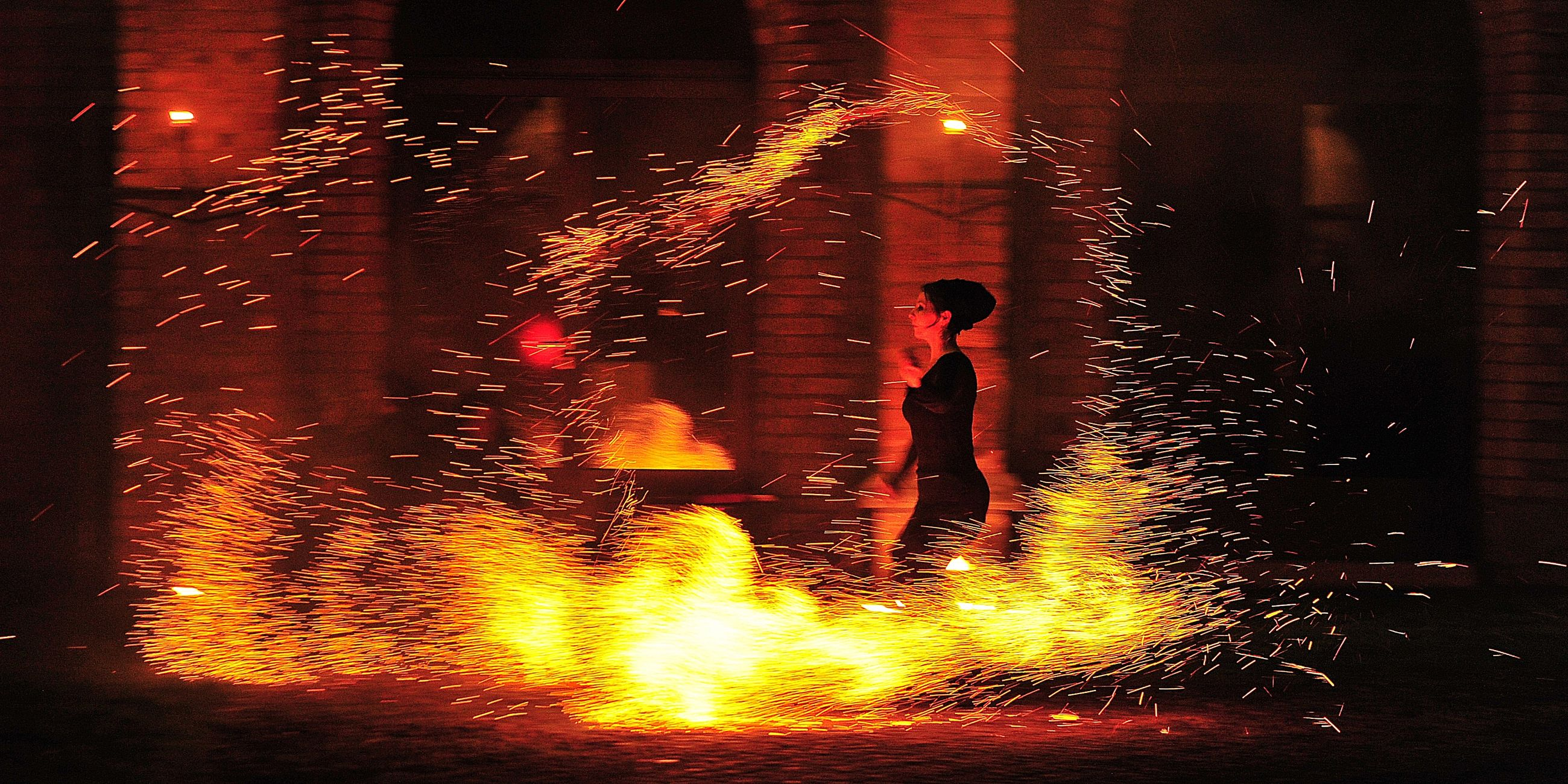 night, glowing, real people, burning, motion, men, firework display, illuminated, heat - temperature, firework - man made object, long exposure, outdoors, flame, lifestyles, water, standing, one person, people