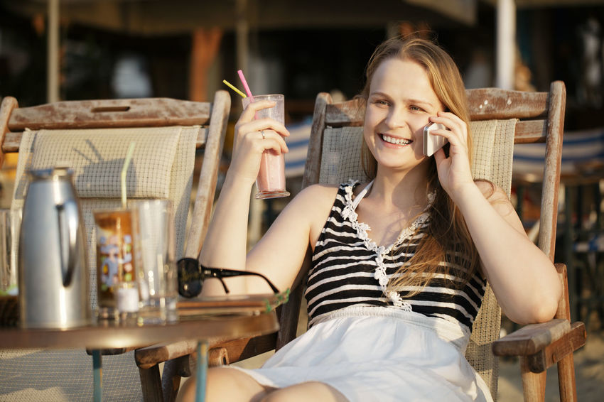 Beach Caucasian Cell Phone  Cellphone Chair Cocktail Comfortable Communication Female Girl Leisure Relax Smart Phone Smile Woman Young Adult