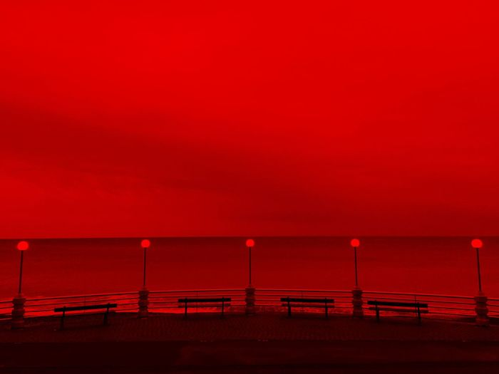 By the sea, evening light, red vision, horizon over the sea and street lamps