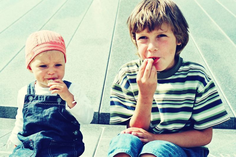 Siblings eating candies while sitting outdoors