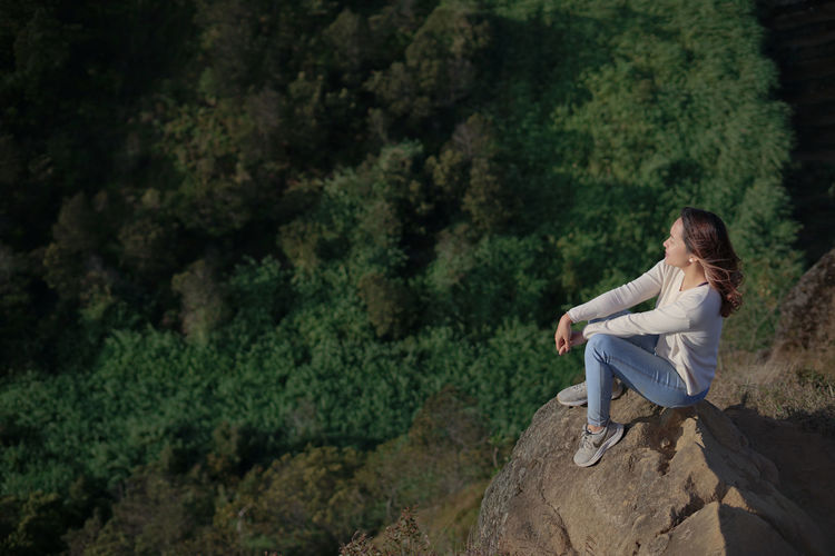 Woman sitting on rock of a mountain
