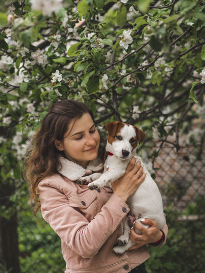 Beautiful woman with dog standing against tree outdoors