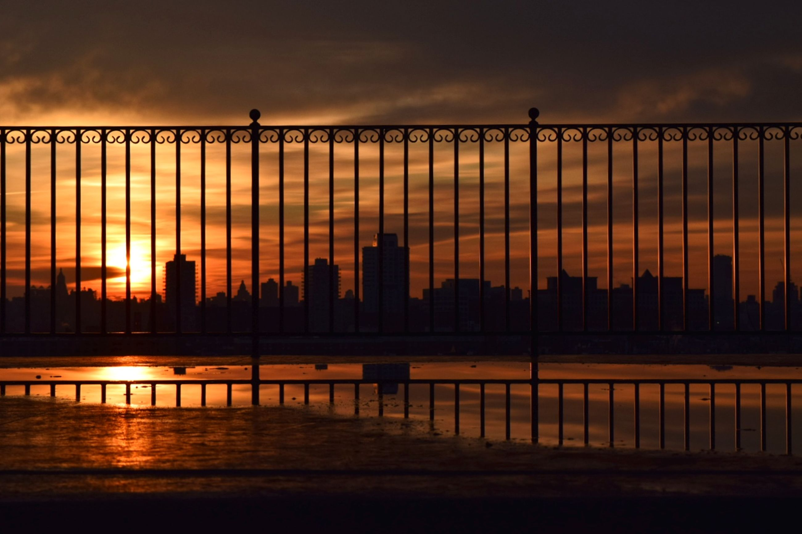 sunset, sky, silhouette, architecture, cloud - sky, building exterior, orange color, built structure, water, nature, outdoors, reflection, river, city, waterfront, scenics, travel destinations, beauty in nature, cityscape, no people, skyscraper, urban skyline