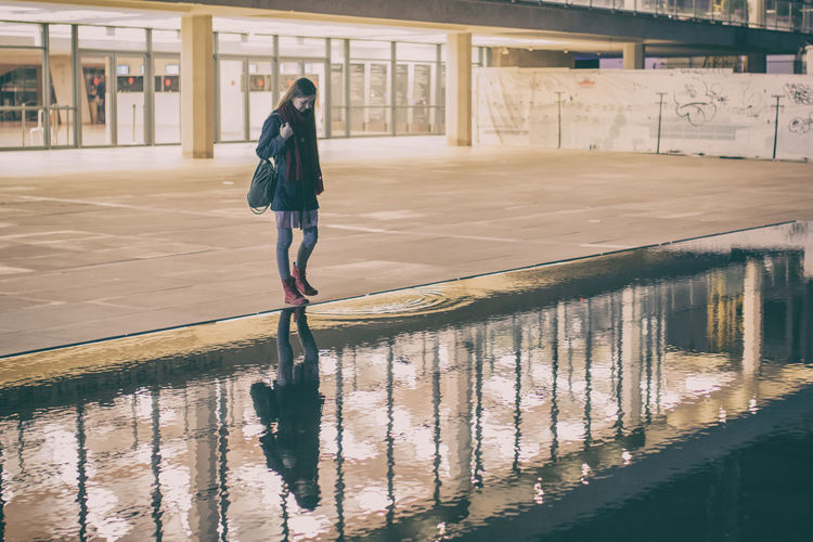 Full length of woman reflecting in water at habima square during night