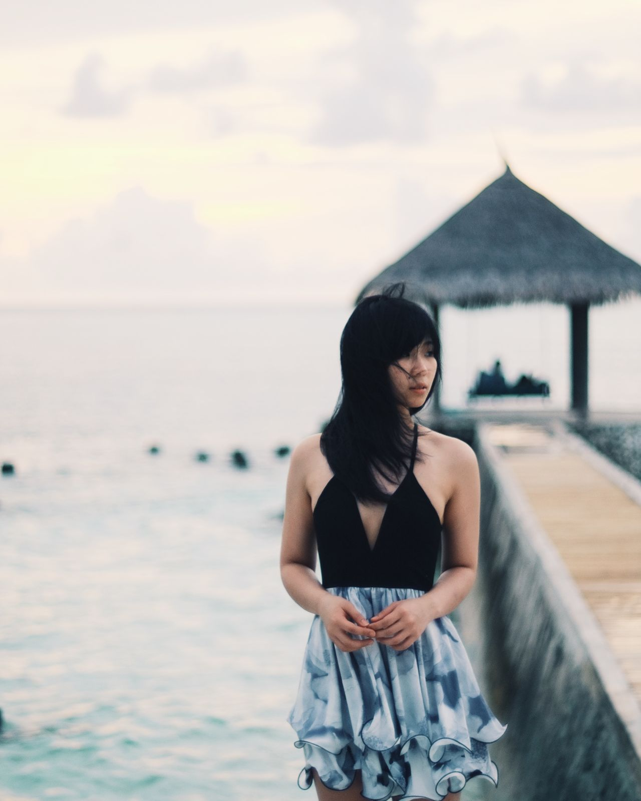 Sensuous woman standing by pier at seaside