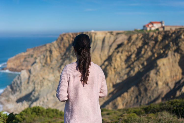 Rear view of woman looking at rock
