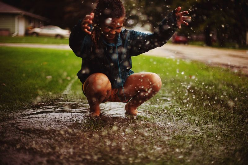 Girl playing in puddle at lawn during rainy season